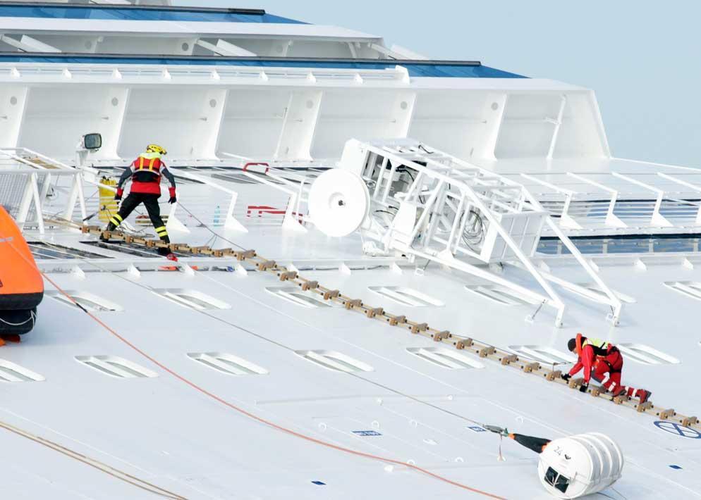 I soccorritori utilizzano le scalette pieghevoli (biscagg�ne) per scalare le fiancate che adesso sono adagiate in posizione quasi orizzontale. L'inclinazione laterale della nave supera gli 80� (Reuters)