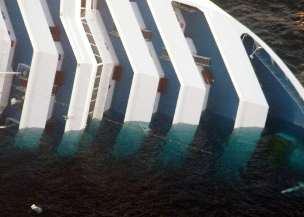 Le acque trasparenti del Giglio lasciano intravedere la parte sommersa del relitto, in questa immagine ripresa dall'elicottero della Guardia di Finanza (Olycom)