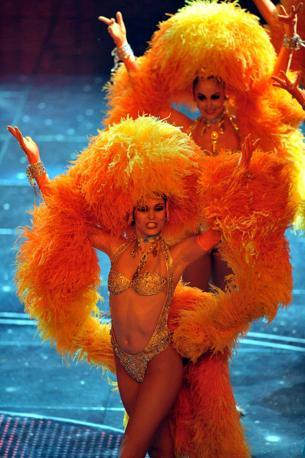 Il teatro Ariston ha aperto le porte al Moulin Rouge. In apertura Daniel Ezralov ha citato il film di Baz Luhrman introducendo il corpo di ballo del più celebre Music Hall di Parigi in uno sgargiante costume di piume gialle e arancioni (Infophoto)