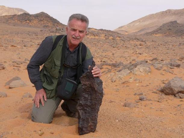 Il professor Mario Di Martino, astronomo dell'Inaf, con un frammento del meteorite che provocò il cratere (per cortesia dell'Istituto nazionale di geofisica e vulcanologia e dell'Istituto nazionale di astrofisica)