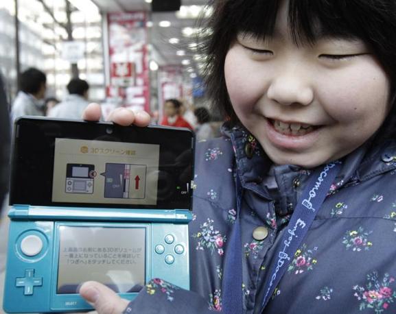 Code, acquirenti esultanti e un po' di colore nei quartieri di Tokyo per il lancio del 3DS, console portatile che propone immagini in tre dimensioni senza bisogno di usare gli occhialini (Ap)