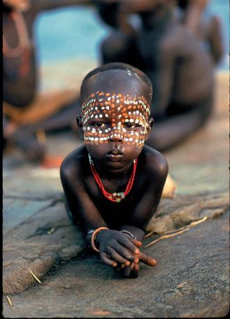 Una bambina Surma. I puntini tratteggiati sul suo volto sono ottenuti con un piccolo ramo intinto alternativamente nel gesso e nell?ocra (Beckwith/Fisher)