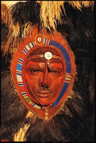 Guerriero masai (Kenya) con il viso coperto da un impasto di grasso di latte mescolato a pigmento rosso ricavato dal terreno. Intorno al volto piume di struzzo ornate di perline (Beckwith/Fisher)