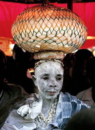 Un sacerdote ashanti del Ghana, cosparso di caolino bianco, trasporta sulla testa un recipiente con pozioni terapeutiche (Beckwith/Fisher)