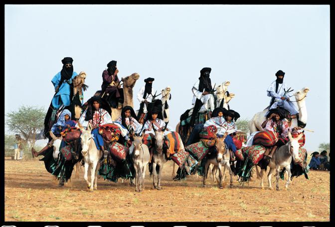 In occasione di un invito a nozze, le donne Tuareg arrivano agghindate a dorso di asino, cariche di coperte e cuscini di pelle, mentre gli uomini le sovrastano sui loro cammelli (Beckwith/Fisher)