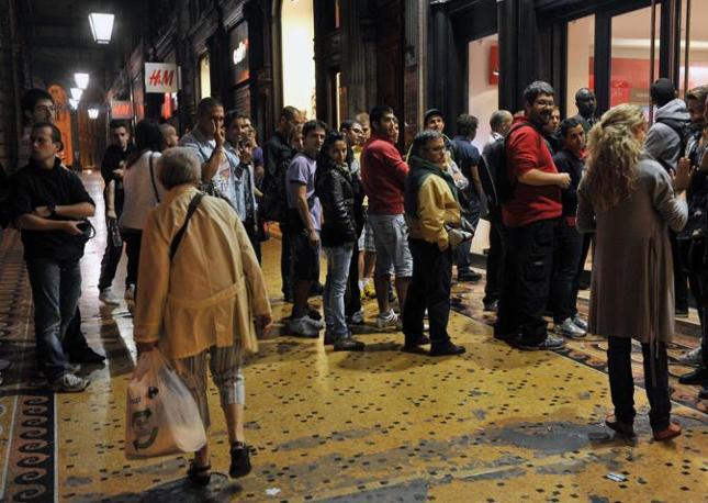 Una anziana signora (s) con la sua borsa della spesa osserva incuriosita la coda dei clienti in fila per impossessarsi per primi del nuovo iPhone davanti al centro Vodafone nel centro di Genova (Ansa)