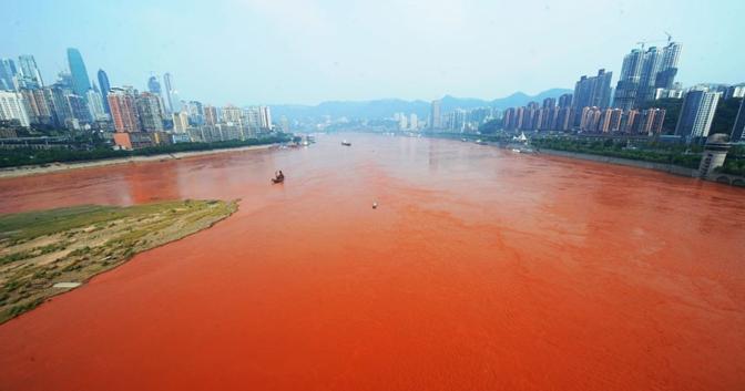 Lo Yangtze, il fiume più lungo dell'Asia, chiamato anche Fiume Azzurro, si è presentato con le acque rosse nei pressi di Chongqing alla confluenza con il Jialin (China Press)