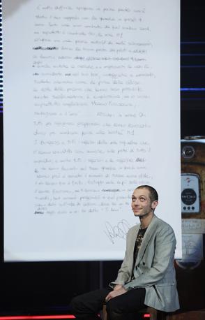 Valentino Rossi ospite del Chiambretti Night su Canale 5 accanto a una gigantografia della lettera d addio scritta alla Yamaha questa sera durante la registrazione del programma (Ansa)