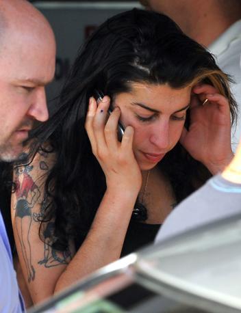 Una delle più recenti foto di Amy Winehouse, al suo arrivo all'aeroporto di Belgrado, lo scorso giugno, appena prima del suo ultimo concerto (Afp)