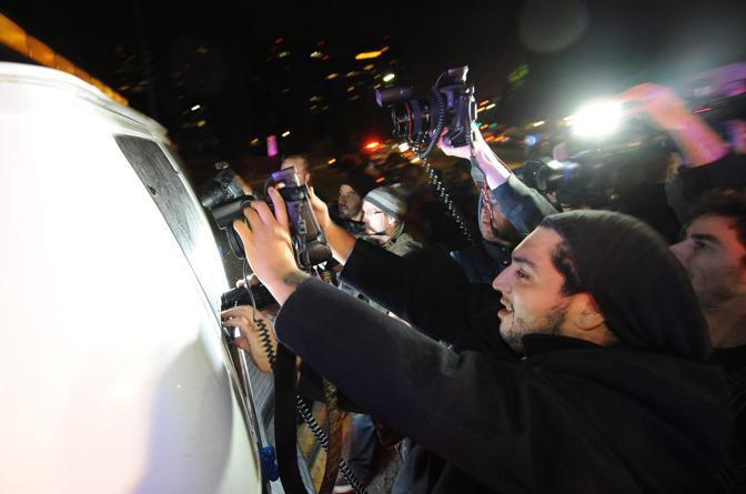 I fotografi cercano di immortalare il corpo della Houston mentre il van del coroner lascia l'alberga (Epa)