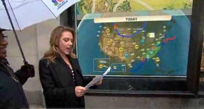 �Meteorina� per un giorno: Scarlett Johansson legge le previsioni del tempo al posto di Al Roker, colpito da una forma di laringite. � lui a proteggere Scarlett con un ombrello (Olycom)