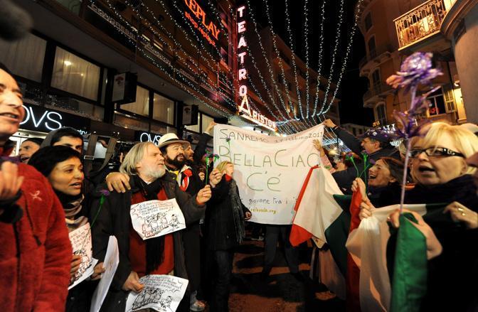 I manifestanti del Popolo Viola cantano Bella Ciao davanti al teatro Ariston (Ansa)