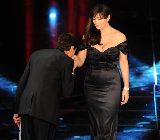 Gianni Morandi saluta Monica Bellucci facendo il baciomano (Infophoto)