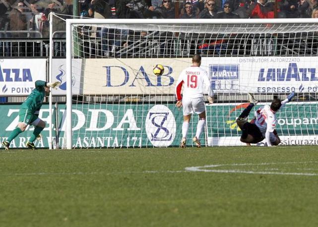 Cagliari-Bari 3-1: il centrocampista del Cagliari Daniele Conti anticipa il difensore Andrea Masiello e sigla il terzo gol per il Cagliari (Ansa)
