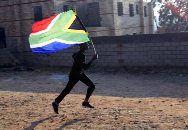 Un tifoso corre per le strade di Soweto (Reuters)