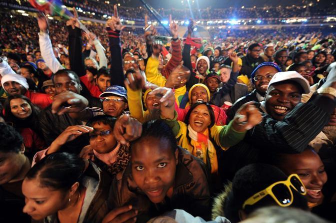 Una folla di migliaia di persone allo stadio Orlando, nella township di Soweto, per il primo atto della cerimonia di apertura dei Mondiali di calcio 2010 in Sudafrica: il grande concerto. Sul palco Shakira, ha cantato «Waka Waka» (È il momento dell'Africa), inno ufficiale della Coppa del Mondo. Con lei il gruppo pop sudafricano Freshlyground. Folla entusiastica ha acclamato il gruppo hip hop americano Black Eyed Peas, il colombiano Juanes, gli americani Alicia Keys e John Legend. E, ancira, diverse star africane: Angélique Kidjo, del Benin, Amadou e Mariam del Mali e Soweto Gospel Choir. STretta di mano fra Sepp Blatter, presidende Fifa, e Jacob Zuma, presidente Sud Africa  (Afp)