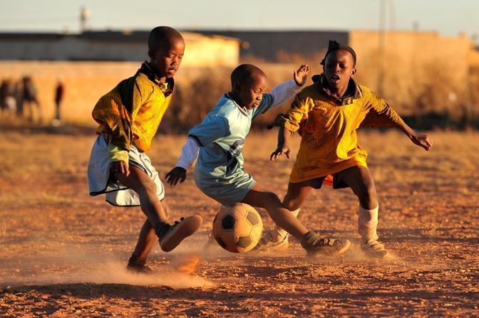 Festa «mondiale» e festa popolare. Vissuta, come nelle parole dell'inno, Whaka waka (È il tempo dell'Africa) la Coppa del Mondo è vissuta come speranza oltre che nello stadio per le strade e nelle thownship più povere del mondo. Nella foto, alcuni bambini giocano a calcio, nella polvera della township di Soweto (Italyphotopress)