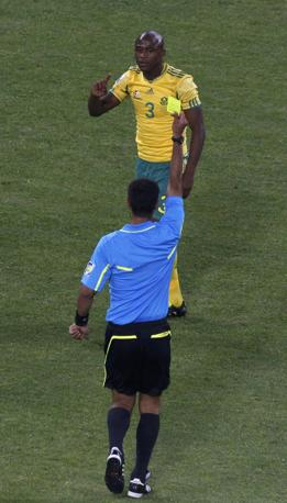 Tsepo Masilela si prende un cartellino giallo dall'arbitro uzbeko Irmatov (Reuters/David Gray)