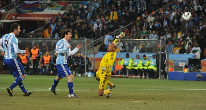 Argentina-Messico: Lionel Messi guarda la palla che supera Oscar Perez