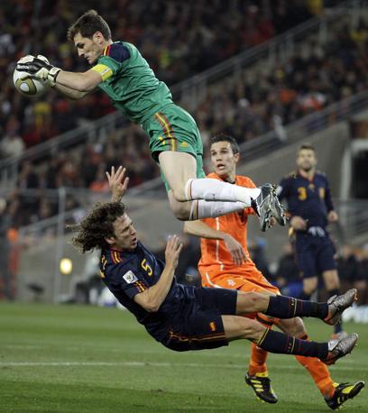 Il portiere spagnolo Iker Casillas nella foga di anticipare Van Persie finisce col travolgere il compagno di squadra Carles Puyol (Matt Dunham / Ap)