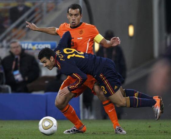 Lo spagnolo Pedro perde l'equilibrio in un contrasto con l'olandese Van Bronckhorst  (Marcos Brindicci / Reuters)