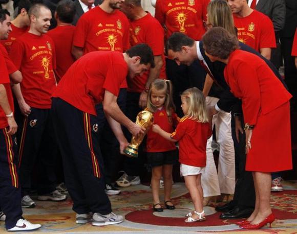 Le principessine Sofia (a destra) e Leonor giocano con la coppa sotto lo sguado del padre, il principe Felipe, e della nonna regina Sofia tutta in rosso come i colori della squadra (Reuters/Andrea Comas)