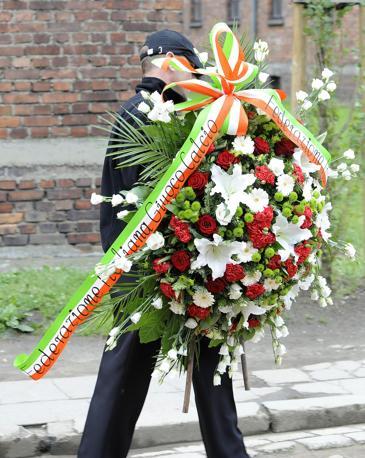 La corona di fiori che la Figc ha voluto fosse deposta ai piedi del muro delle fucilazioni all interno del campo di sterminio di Auschwitz (Ansa/Brambatti)