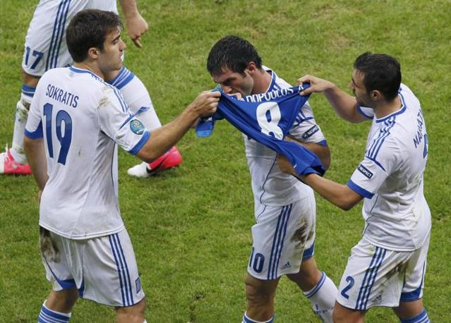 GRECIA-RUSSIA 1-0 - I greci mostrano la maglia del compagno infortunato Avraam Papadopoulos (Reuters/Foeger)