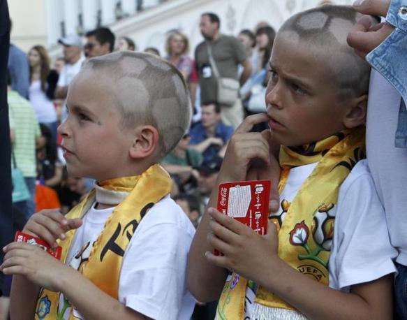 """Due bimbi ucraini con la testa... letteralmente nel pallone"""" (Reuters)"""