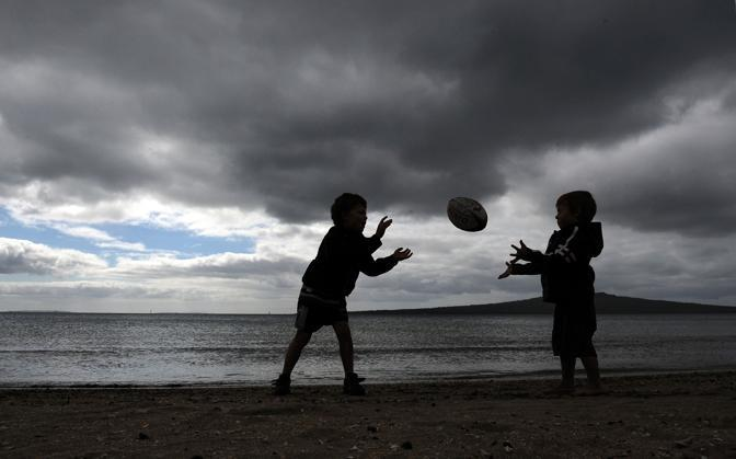 Bambini che giocano - a rugby, ovviamente - sulla spiaggia di Auckland