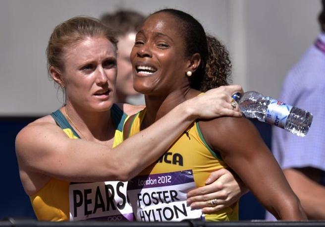 L'atleta giamaicana Brigitte Foster-Hylton consolata dalla collega australiana dopo aver perso i 100 metri (Ap/Meissner)
