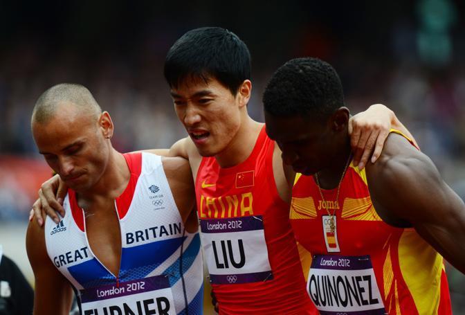 La maledizione dell'Olimpiade: Liu Xiang ancora una volta ha fallito sui 110 ostacoli. Qui viene cavallerescamente aiutato dai colleghi. Come il britannico Andrew Turner che ha vinto la batteria in 13.42 (Afp)