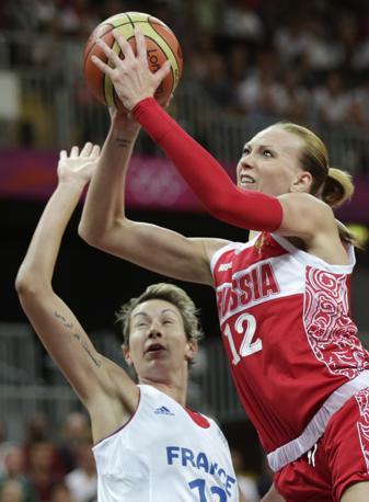 La russia Irina Osipova va a canestro, contrastata invano dalla francese Elodie Godin, durante le eliminatorie del torneo femminile di basket (Ap)
