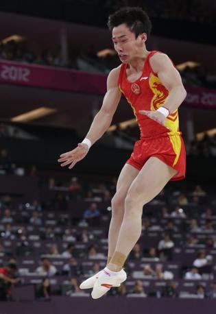 Il cinese Zou Kai effettua un salto durante la prova di corpo libero: vincerà l'oro (Ap)