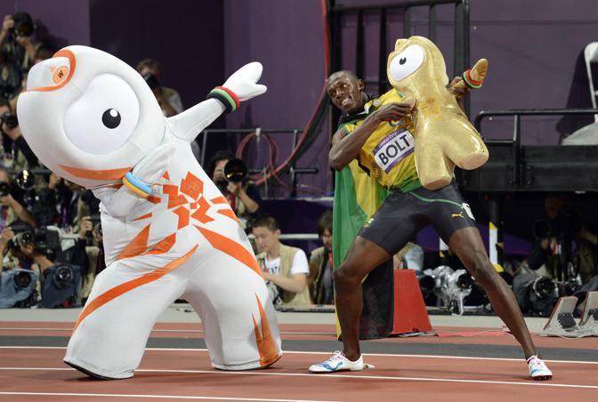 Usain Bolt nella leggedna dei Giochi: bissa il successo di Pechino e vince l'oro sui 100 anche a Londra. E qui festeggia all'Olimpico con la mascotte dei Giochi (Reuters)