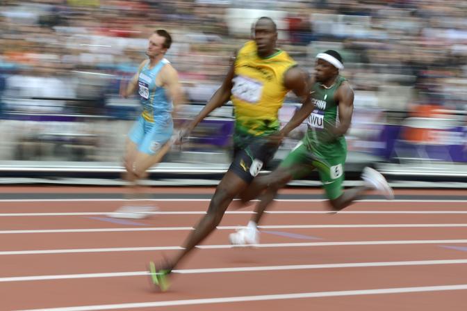 """Dopo aver stravinto i cento, a Usain Bolt è bastato """"passeggiare"""" nei 200 per accedere alle semifinale. Emozioni semmai dopo la qualifica quando il campione ha regalato il suo cappellino a un volontario. Emozionatissimo (Afp)"""