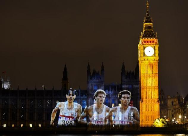 Partecipa anche il Big Ben: Steve Ovett, Steve Cram e Sebastian Coe, i grandi del mezzofondo britannico, proiettati sulla facciata (Afp)