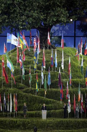 Il presidente del Cio Jacques Rogge sotto alla collina delle bandiere e alla quercia simbolo legge il discorso d'apertura dell'Olimpiade londinese (Ap)