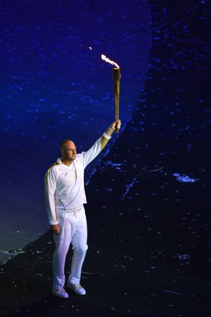 Sir Steve Redgrave, cinque volte oro olimpico per la Gran Bretagna  nel canottaggio, raccoglie la torcia portata con il motoscafo da David Beckham e corre fin dentro lo stadio. Non � lui l'ultimo tedoforo (Afp)