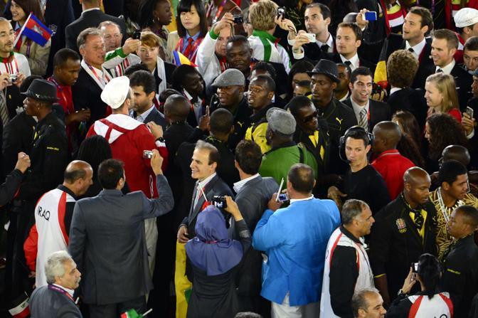 Intanto al centro della pista l'arrivo di Bolt provoca il mischiarsi delle delegazioni: è gara per rubare uno scatto con il giamaicano, re della pista (Afp/MacDougall)