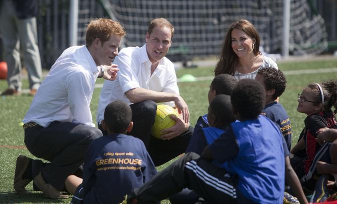 Kate Middleton in compagnia del marito William e del cognato Harry con alcuni giovani studenti del Bacon's college