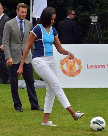 Michelle Obama accenna alcuni palleggi sotto lo sguardo di David Beckham all'iniziativa «Let's Move». Una specie di  riscaldamento prima della cerimonia inaugurale dei Giochi (Afp/Samad)