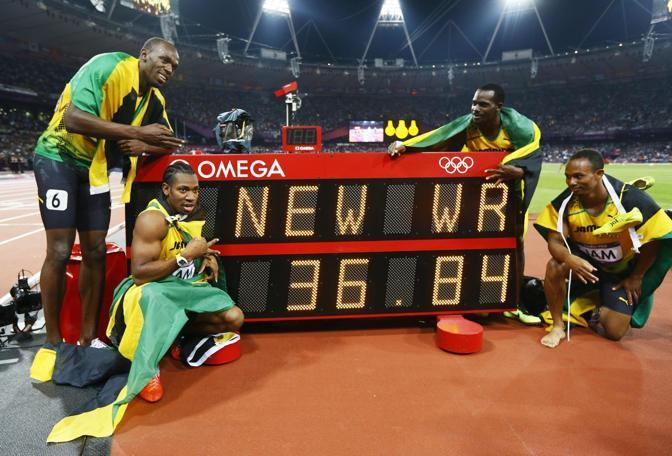 Ed ecco la staffetta giamaicana davanti al tabellone che indica il nuovo record del mondo  (Epa/Okten)