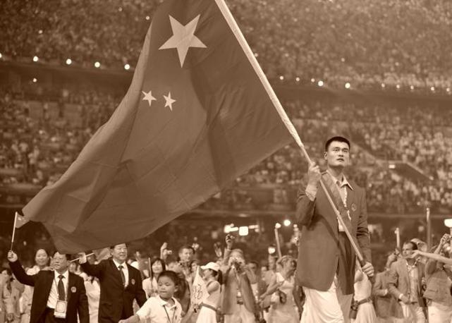 """Yao Ming, portabandiera della Cina, alla sfilata per la cerimonia d'apertura nel """"Nido d'uccello"""", lo stadio olimpico di Pechino (Afp)"""