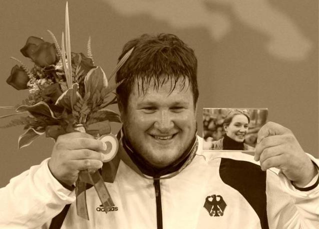 La gioia e il dolore: il tedesco Matthias Steiner vince l'oro nel sollevamento pesi, categoria 105 k, e sul podio mostra la foto della moglie Susann, morta in un incidente stradale nel luglio 2007. A lei, scomparsa tragicamente, ha dedicato il risultato e tutti gli sforzi fatti per conseguirlo (Ansa)