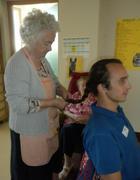 Un'anziana sistema i capelli a un operatore a Griesfeld