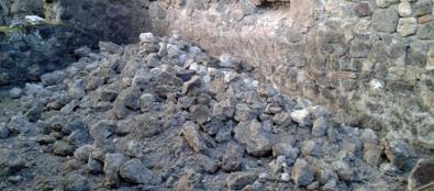 Il muro della bottega nella via Stabiana crollato a Pompei (Ansa)