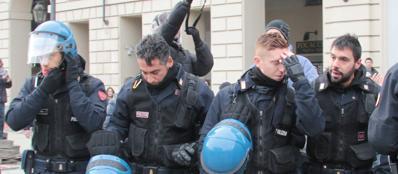 Alcuni poliziotti si tolgono il casco a Torino (Fotogramma)
