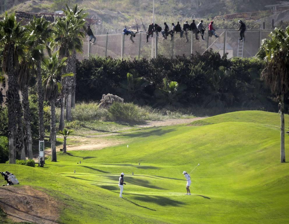 Migranti che cercano di passare sul confine, dentro un campo dal Golf