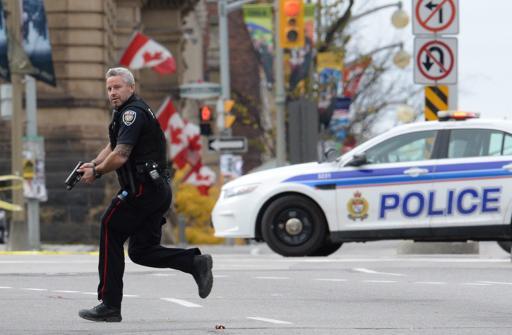 Un poliziotto armato corre fuori dal Parlament Hill di Ottawa  (Ap)